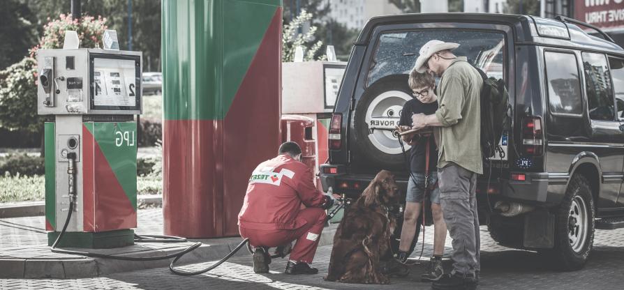 Pracownik Tezet tankujący samochód rodziny z psem, która stoi obok